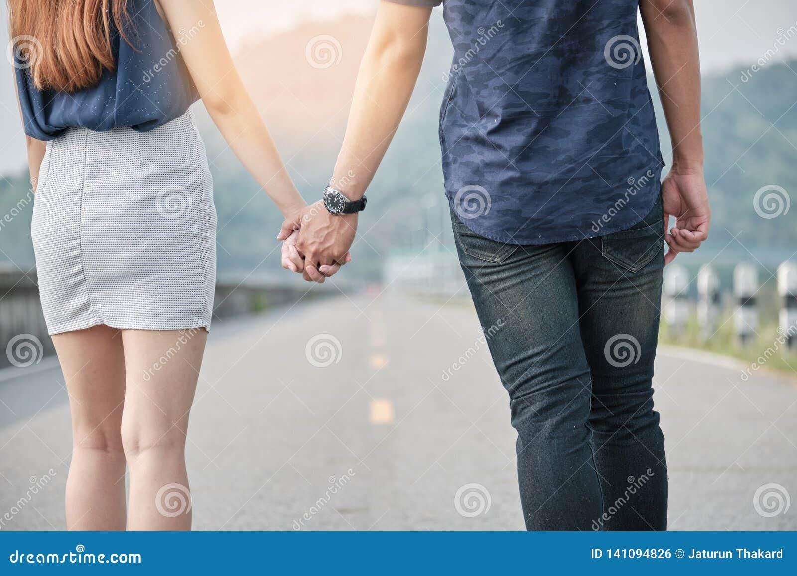 Pares asiáticos jovenes que colocan y que llevan a cabo la mano con amor puro