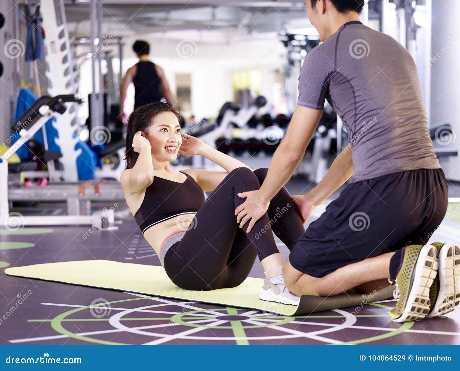 Pares asiáticos jovenes que ejercitan en gimnasio