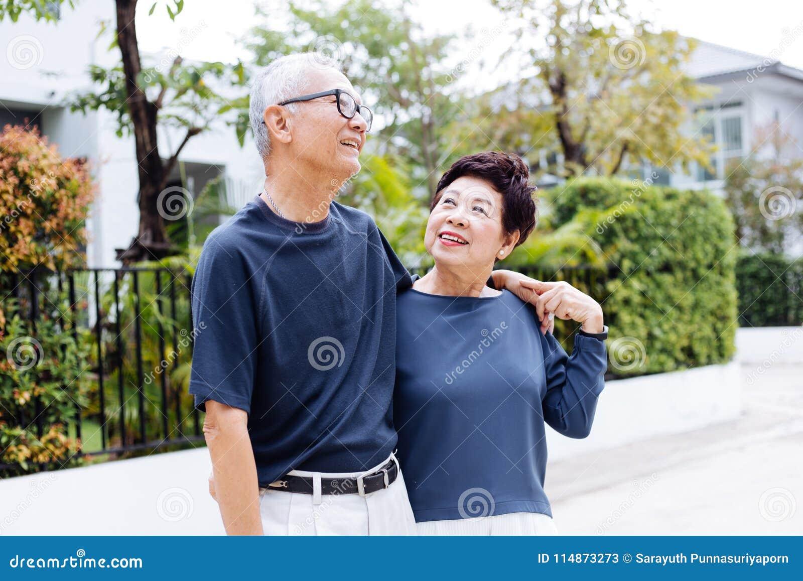Pares asiáticos mayores jubilados felices que caminan y que miran uno a con romance en parque y casa al aire libre en fondo
