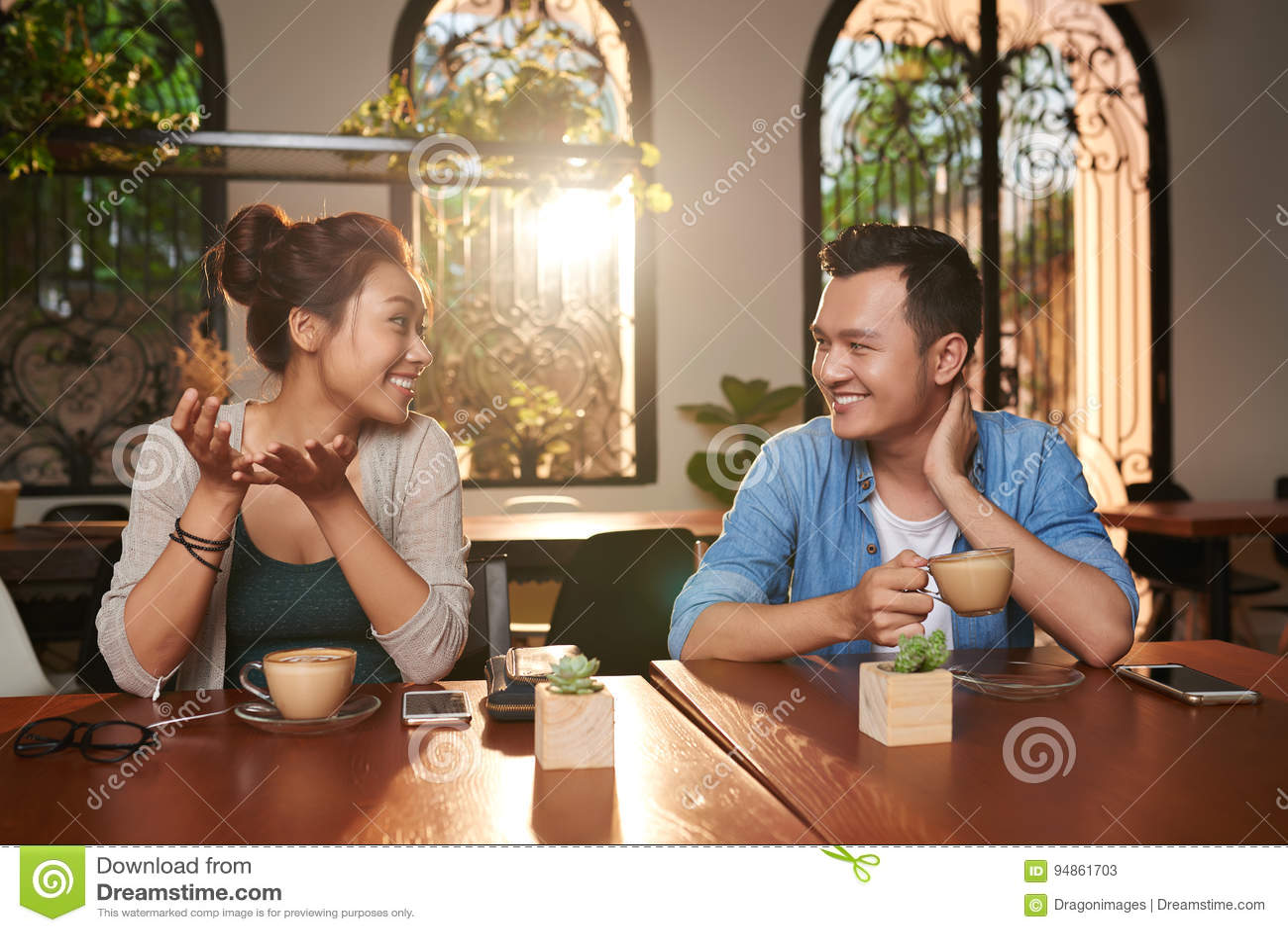 Pares asiáticos que conversam no café