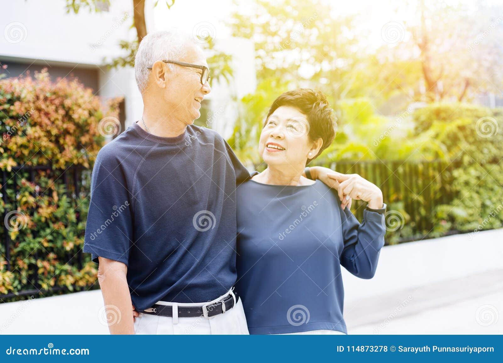 Pares asiáticos superiores aposentados felizes que andam e que olham se com romance no parque e na casa exteriores no fundo