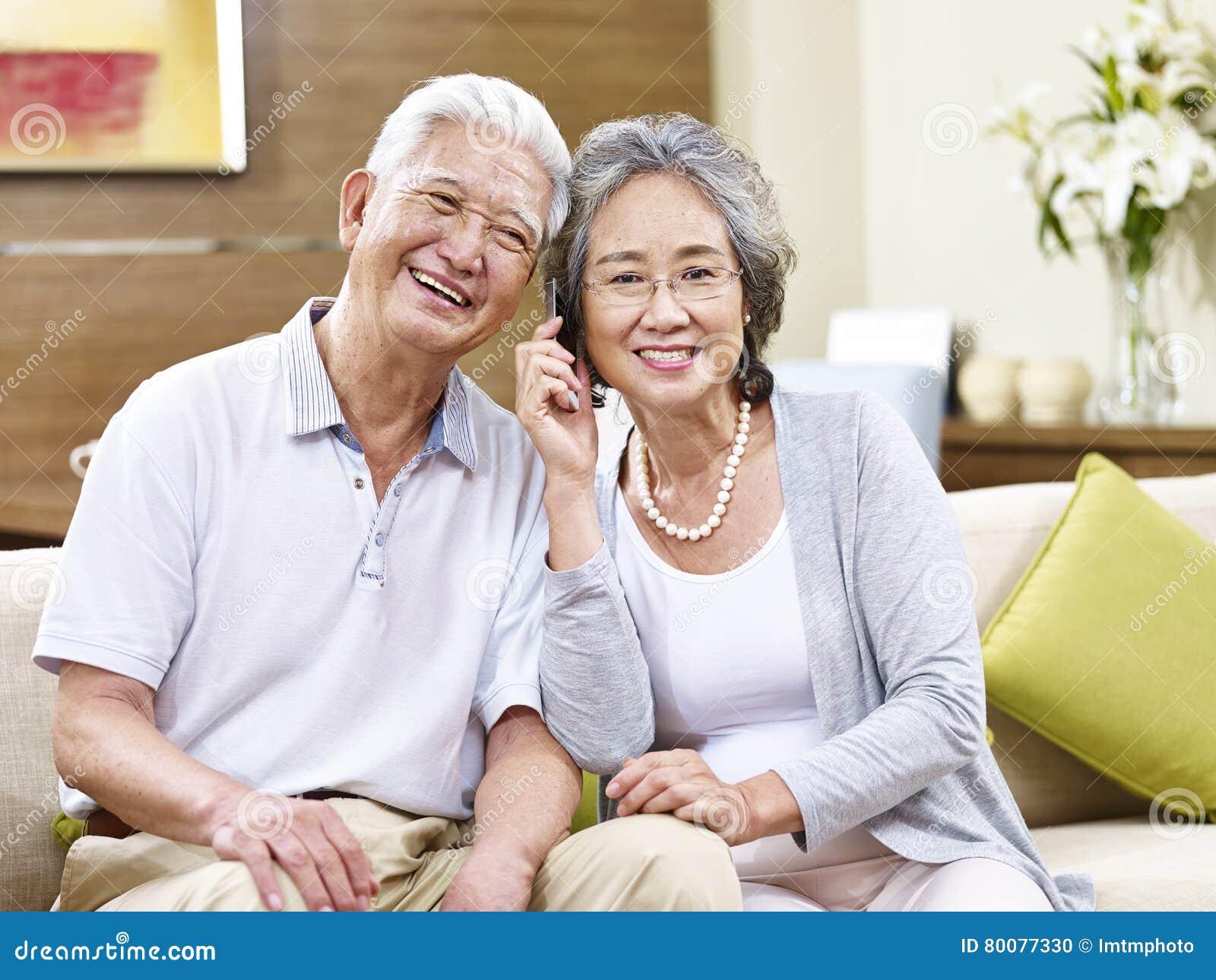 Pares asiáticos superiores que falam no telefone celular