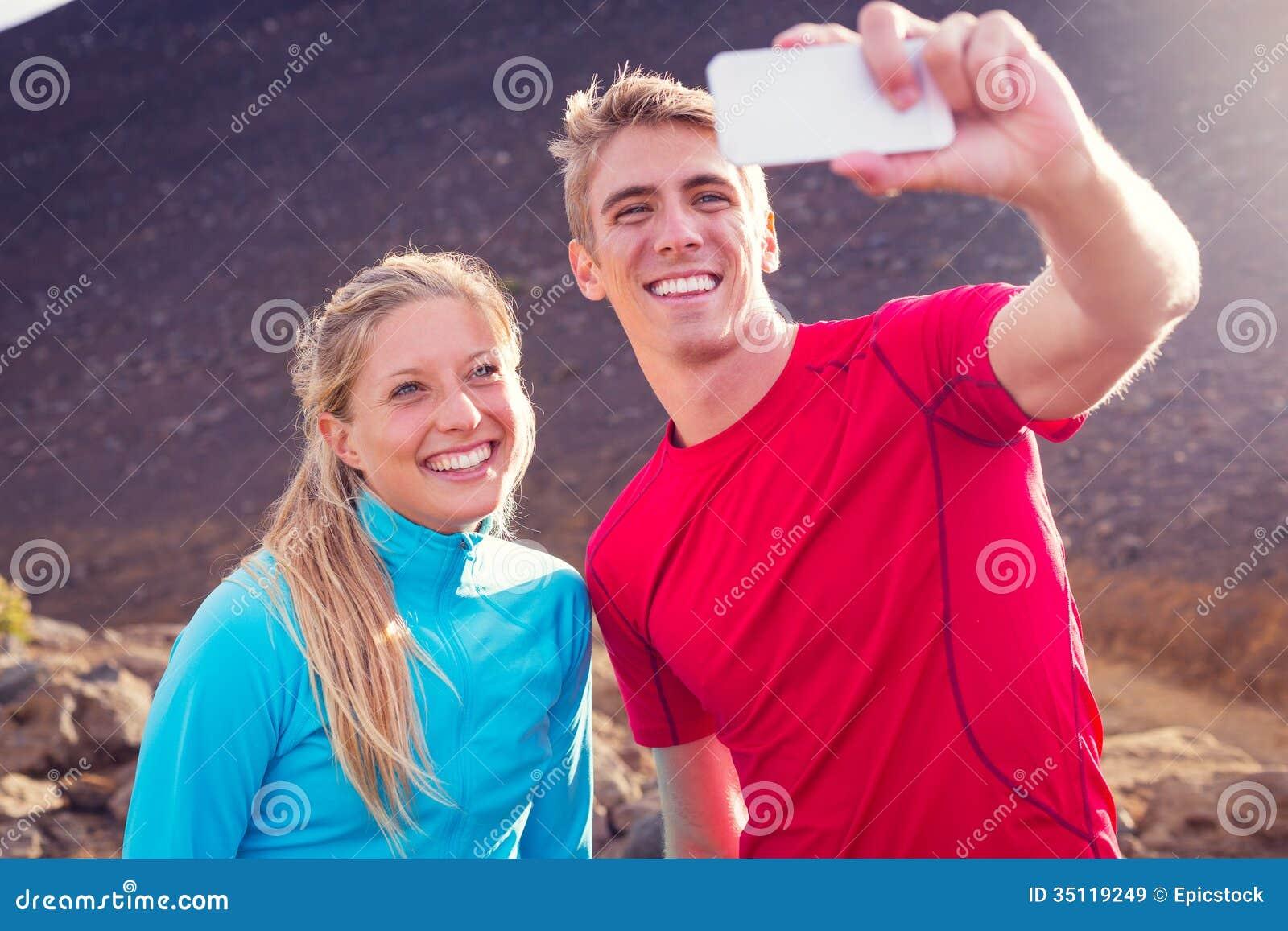 Pares atléticos atractivos jovenes que toman la foto de ellos mismos con