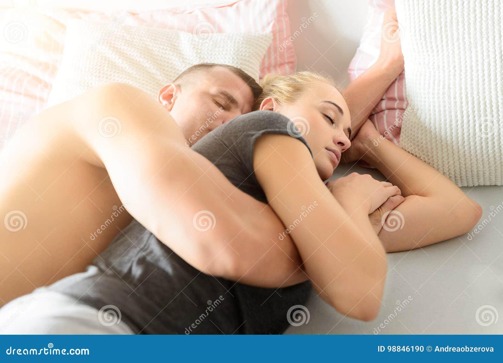 Pares atractivos que duermen junto en la cama que abraza Concepto del amor y de la relación
