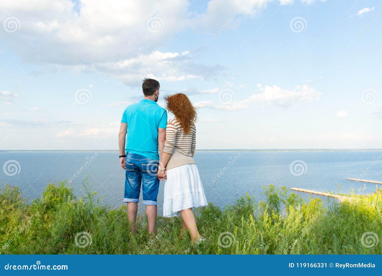 Pares atractivos que se detienen disponible y que miran el lago y el cielo azul con las nubes