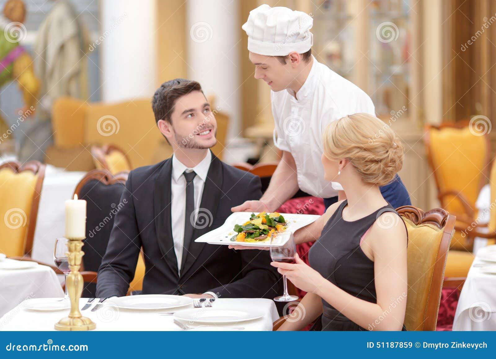 Pares atractivos que visitan el restaurante de lujo