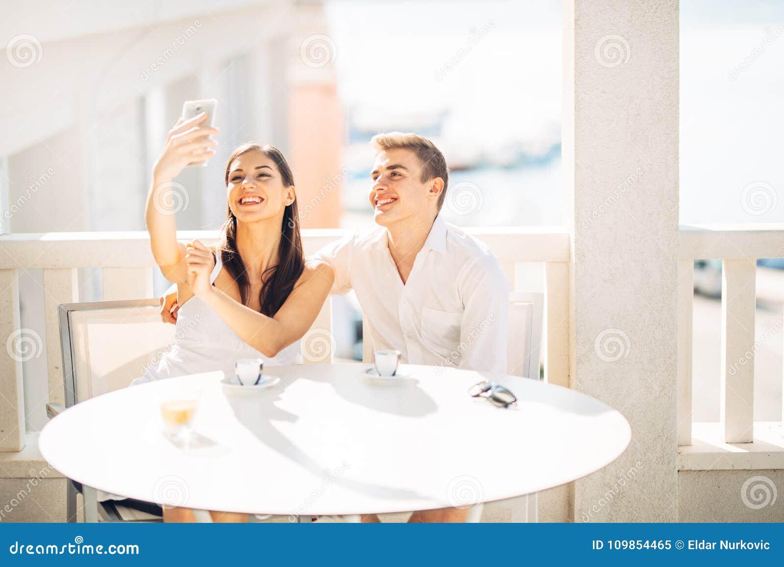 Pares atrativos que têm a primeira data Café com um amigo Povos felizes de sorriso que fazem um selfie com um smartphone