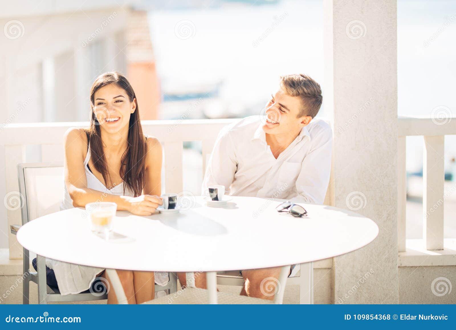 Pares atrativos que têm a primeira data Encontro às cegas Café com um amigo Povos felizes de sorriso que comem um café, datando
