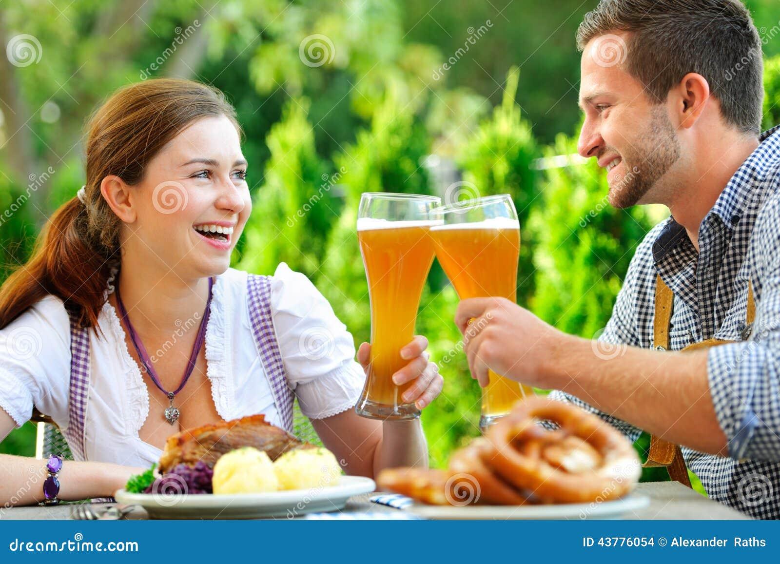 Pares bávaros de sorriso em Oktoberfest