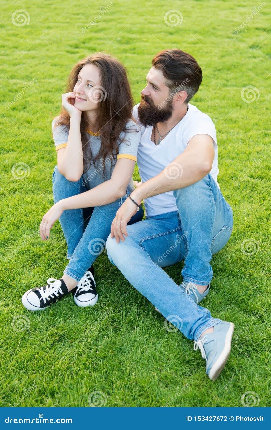 Pares bonitos pares da forma que têm o divertimento junto menina bonito e moderno farpado do homem na grama verde Pares no amor