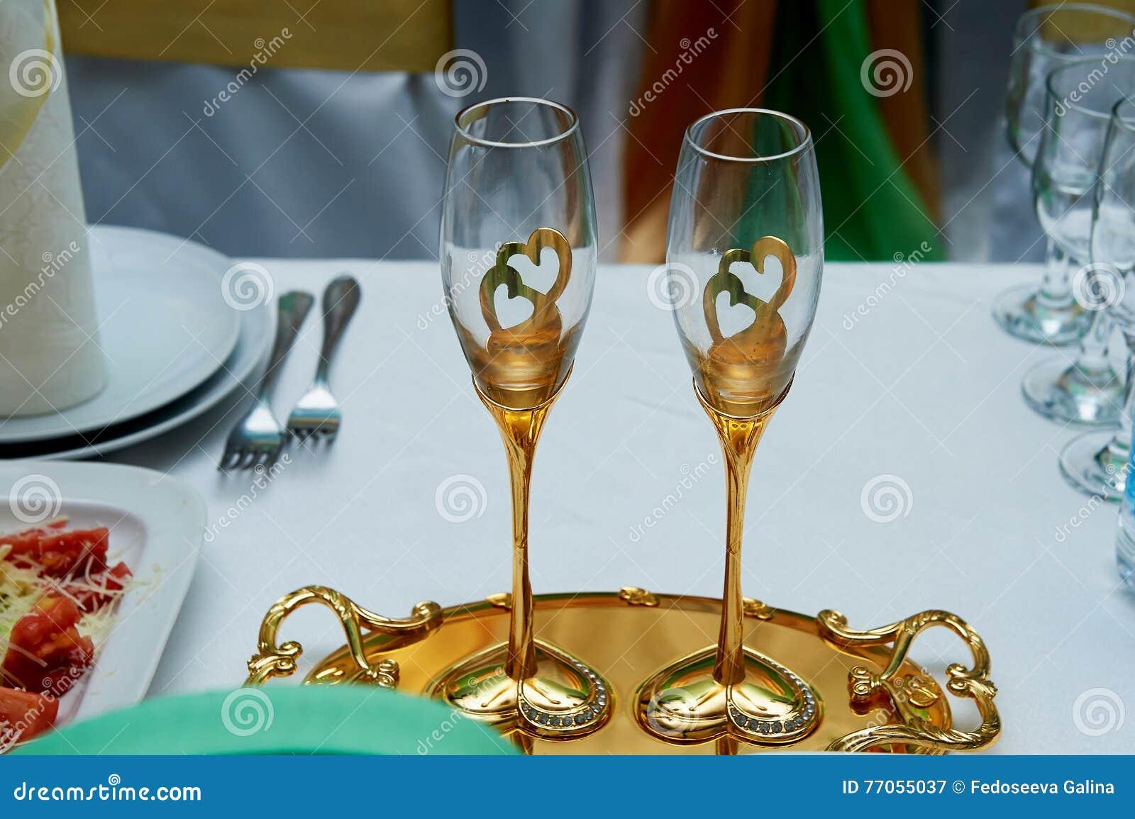 Pares bonitos de cálices do casamento com ouro Em uma bandeja