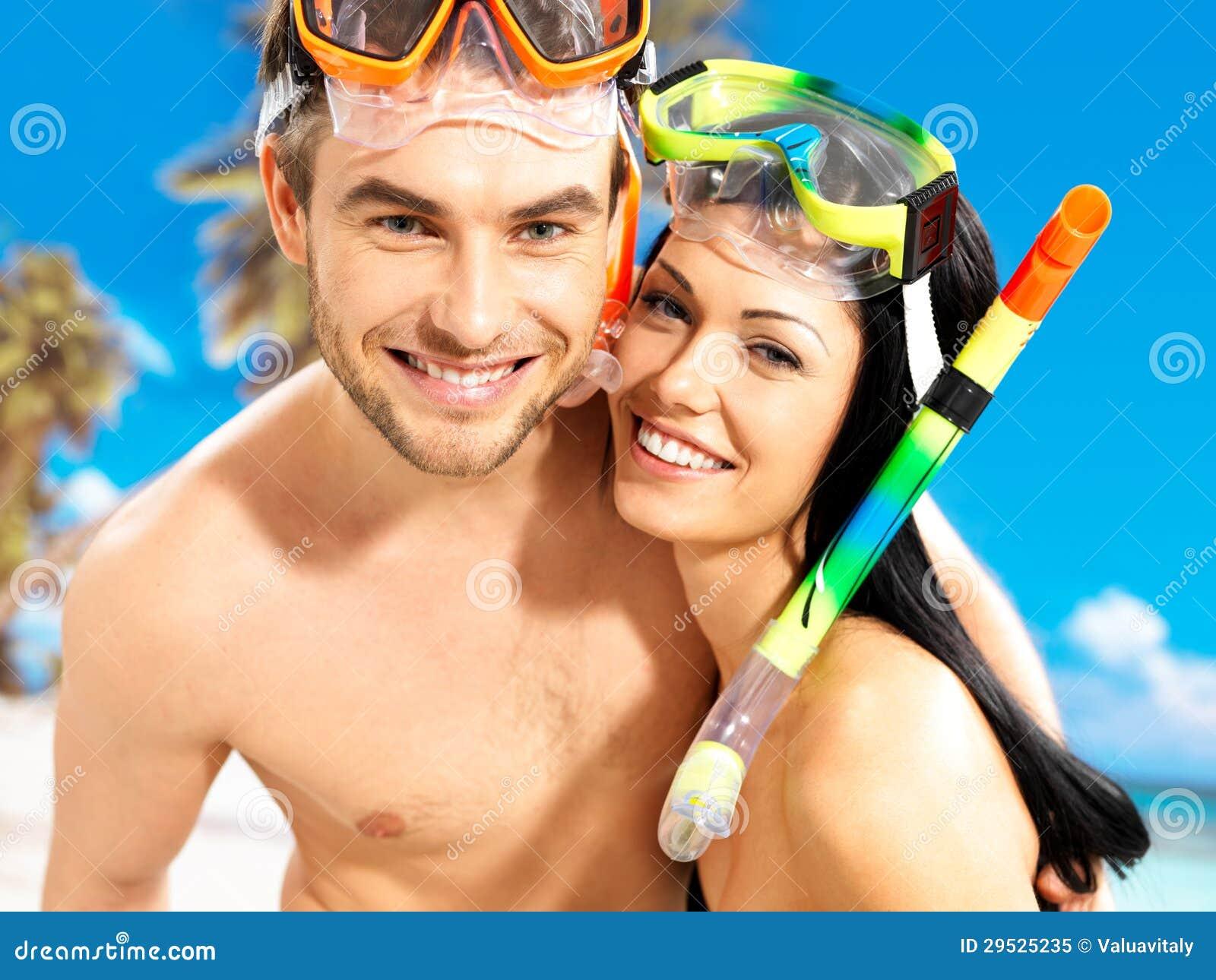 Pares bonitos do divertimento na praia tropical com máscara da natação