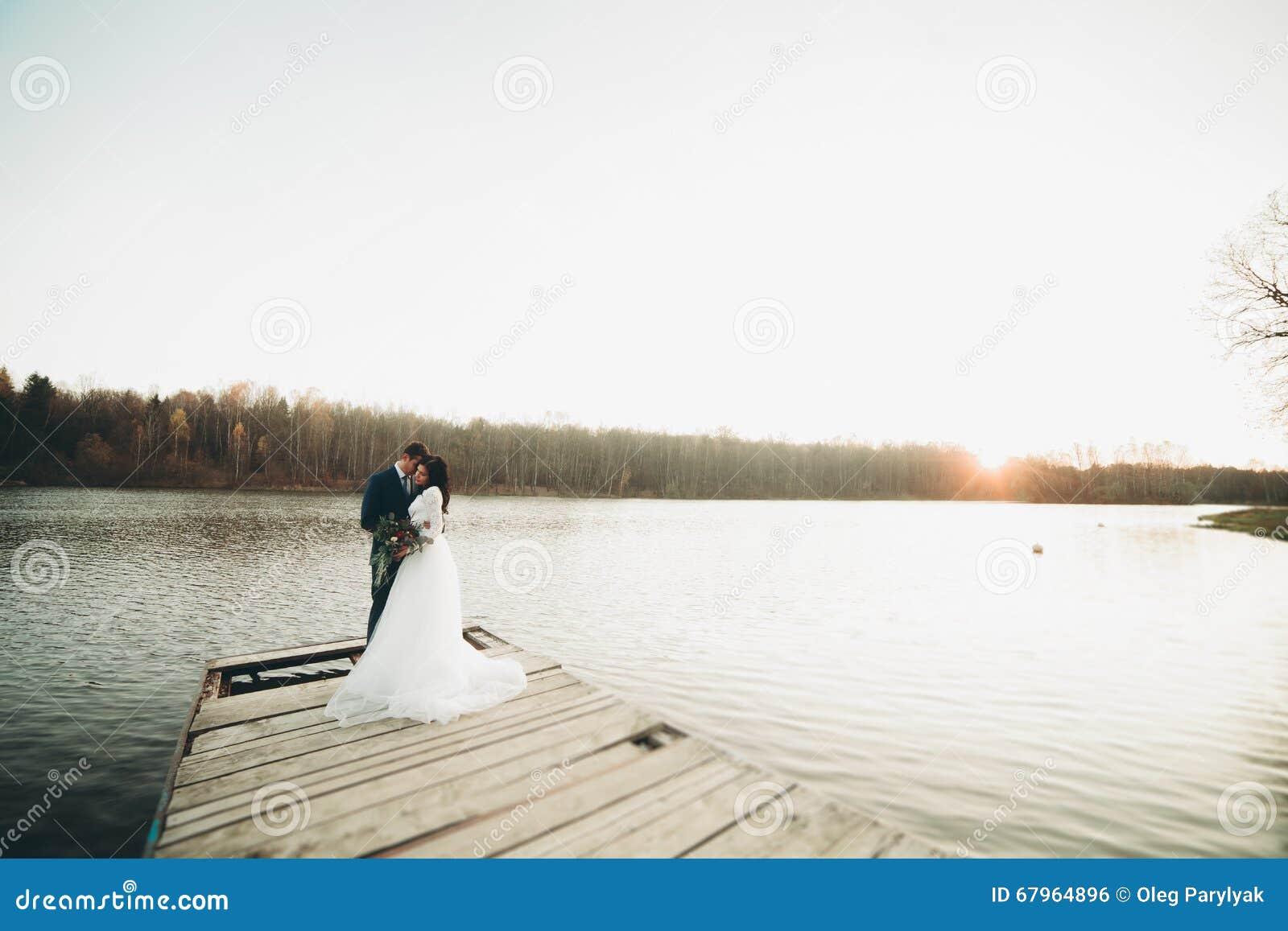 Pares bonitos elegantes do casamento que levantam perto de um lago no por do sol