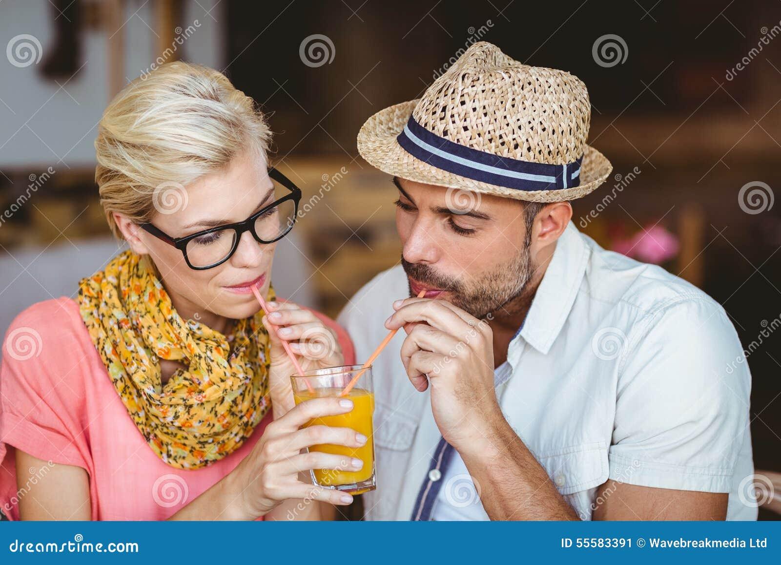 Pares bonitos em uma data que compartilha de um suco de laranja