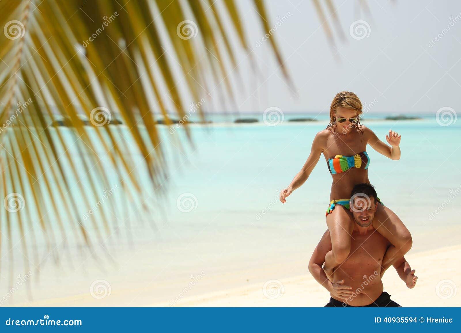 Pares bonitos felizes que apreciam na praia no dia ensolarado h de Maldivas