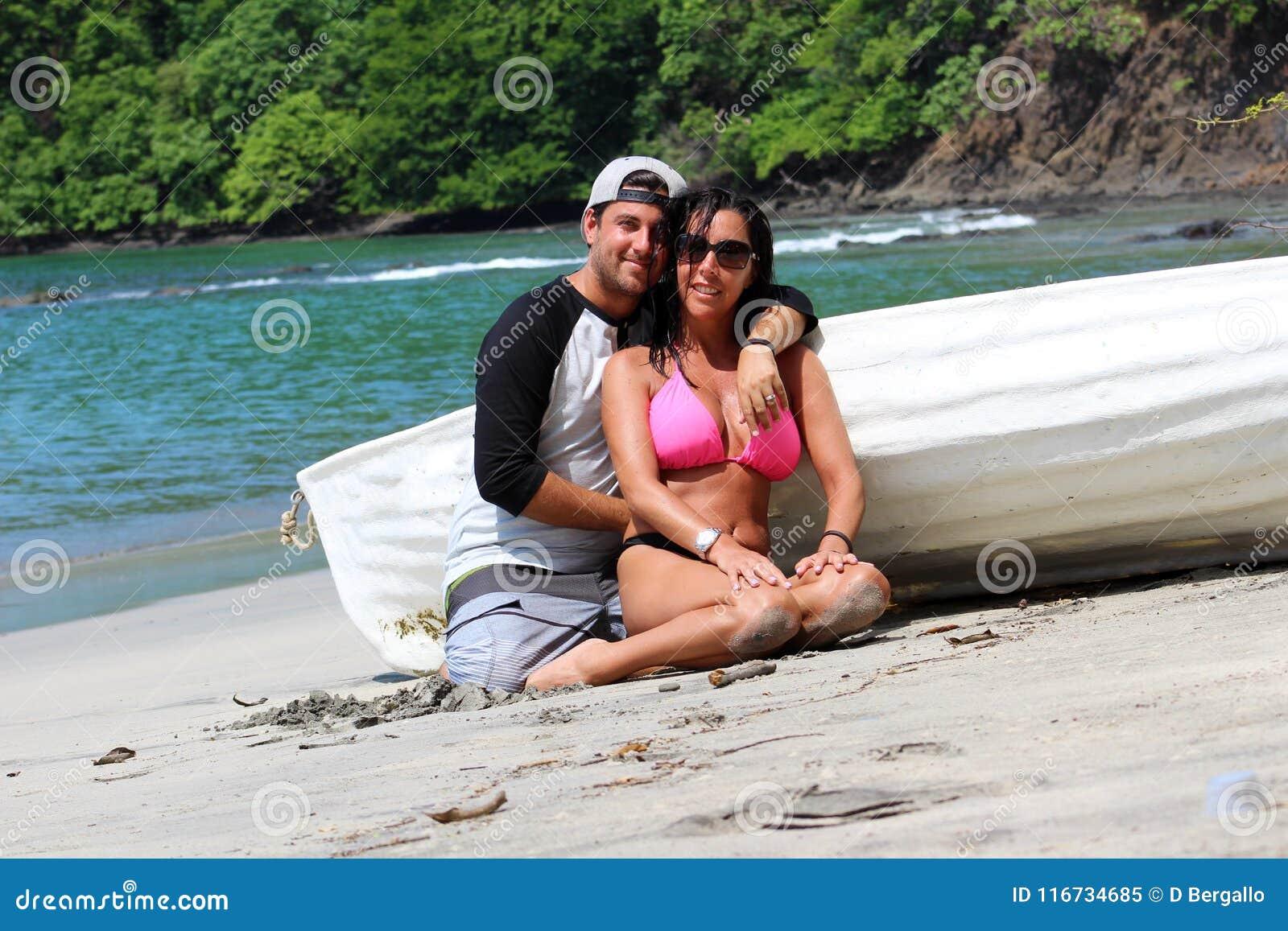Pares bonitos na praia com um barco, uma mulher  sexy  lindo das expressões felizes e um indivíduo latin em Costa Rica