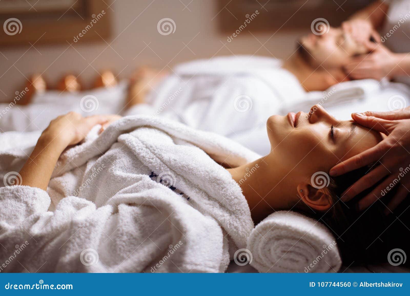 Pares bonitos novos felizes que apreciam a massagem principal nos termas