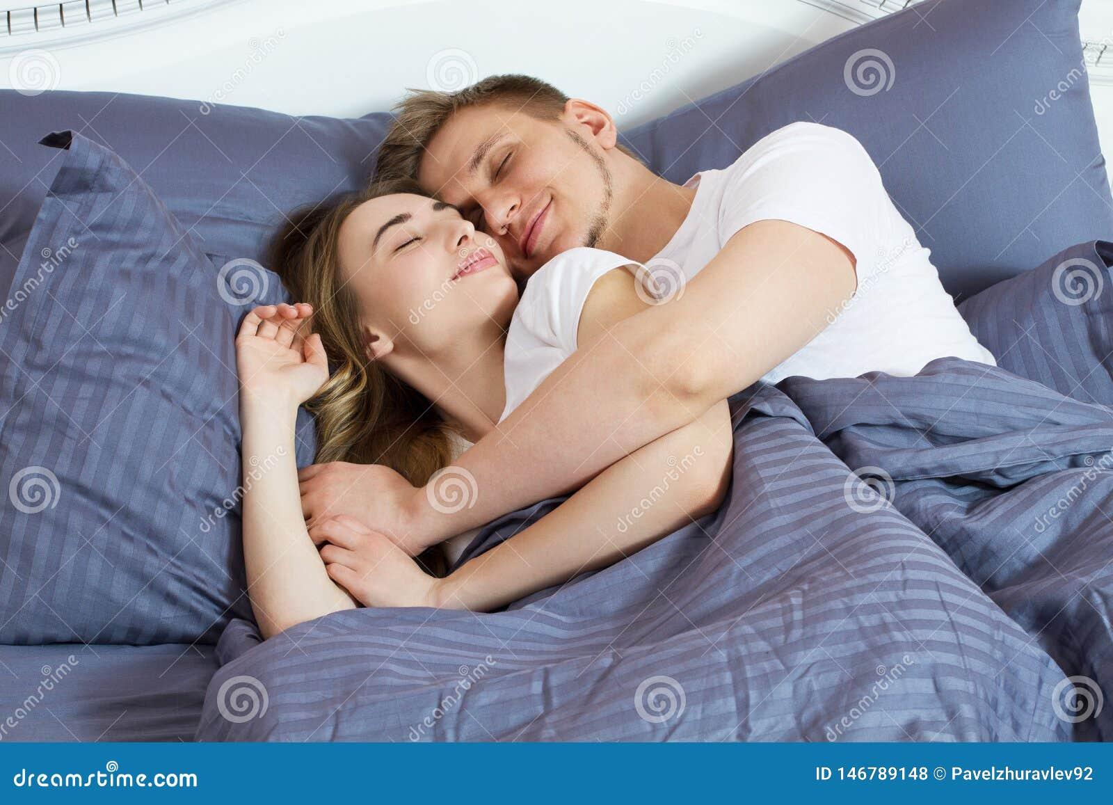 Pares bonitos novos que dormem junto na cama Cama e colchão confortáveis