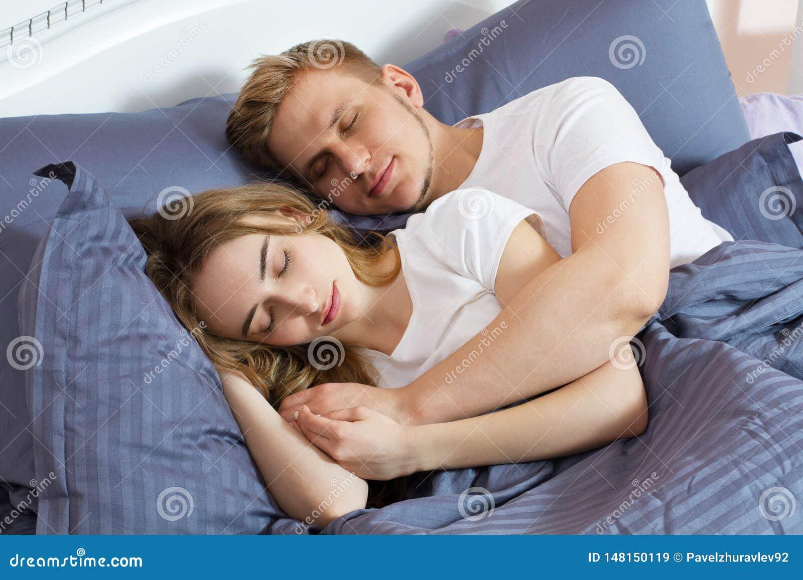 Pares bonitos novos que dormem junto na cama Cama e colch?o confort?veis