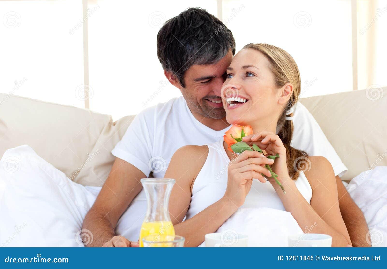 Pares bonitos que comem o pequeno almoço encontrar-se na cama