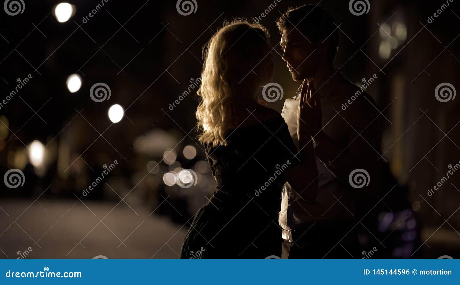 Pares bonitos que guardam as m?os e que aproximam-se ao beijo, data rom?ntica, amor