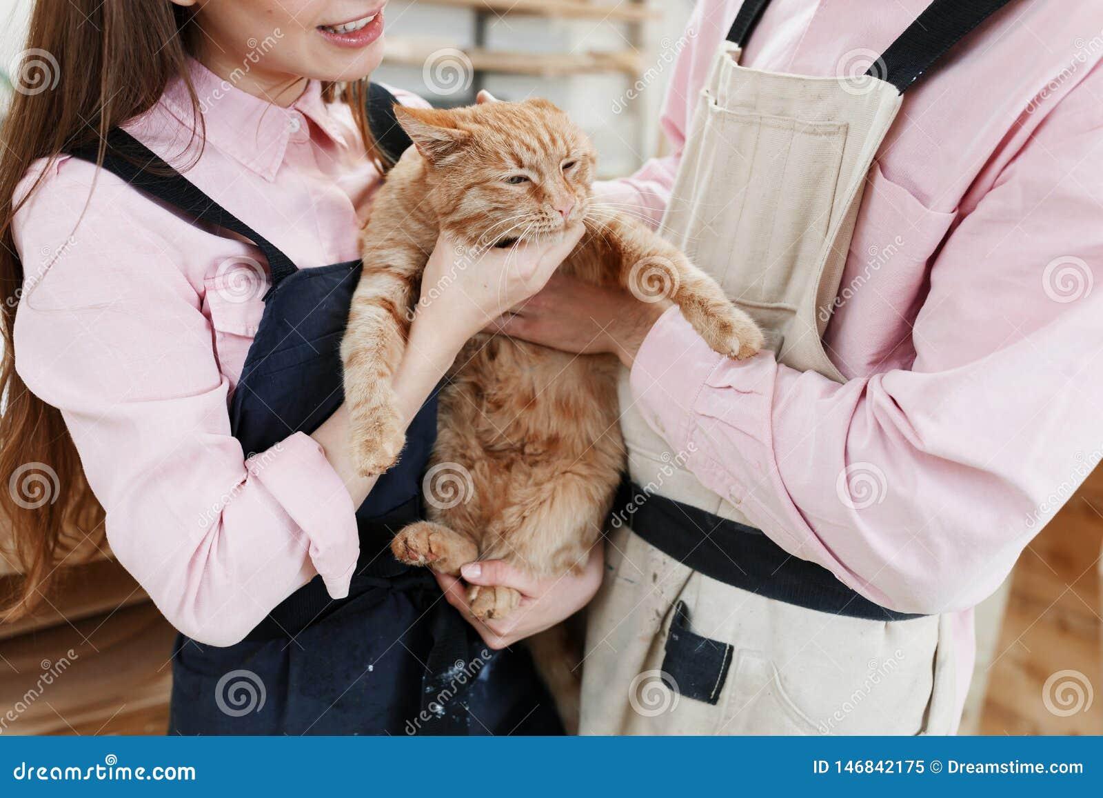 Pares bonitos que relaxam e que jogam com um gato vermelho grande nas mãos