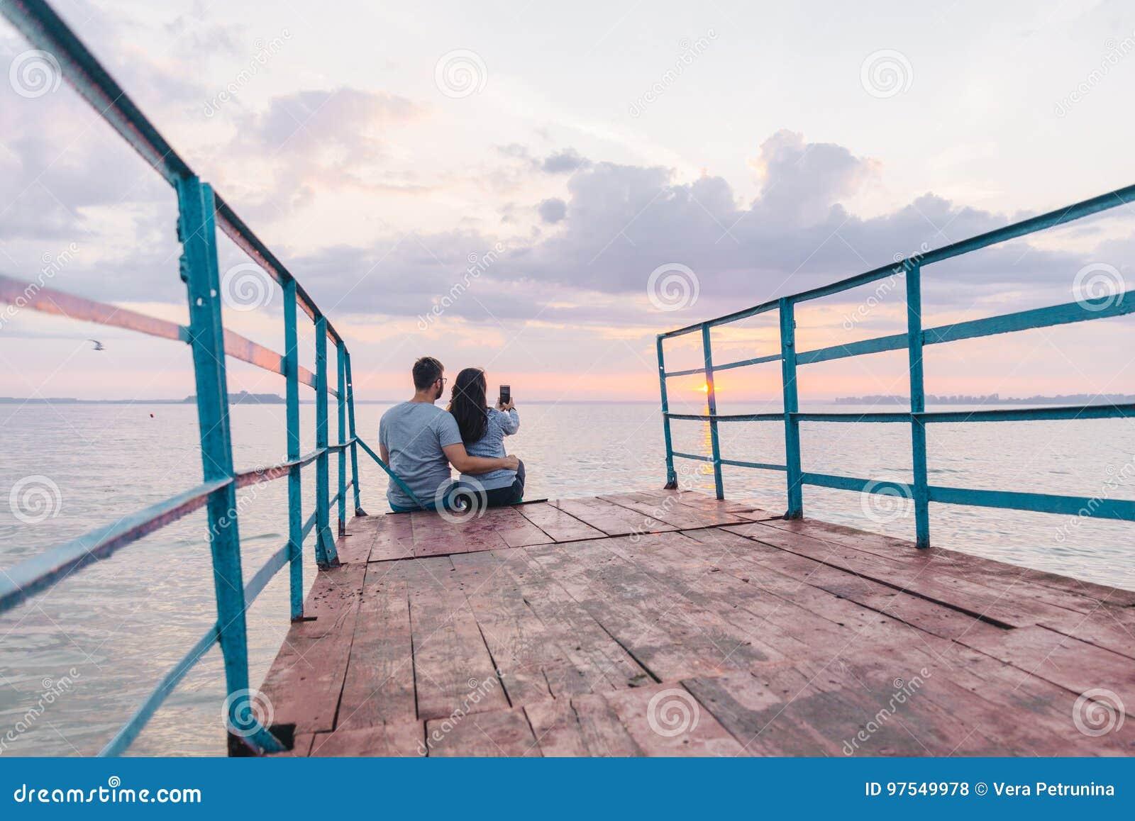 Pares bonitos que sentam-se no cais e que olham no nascer do sol