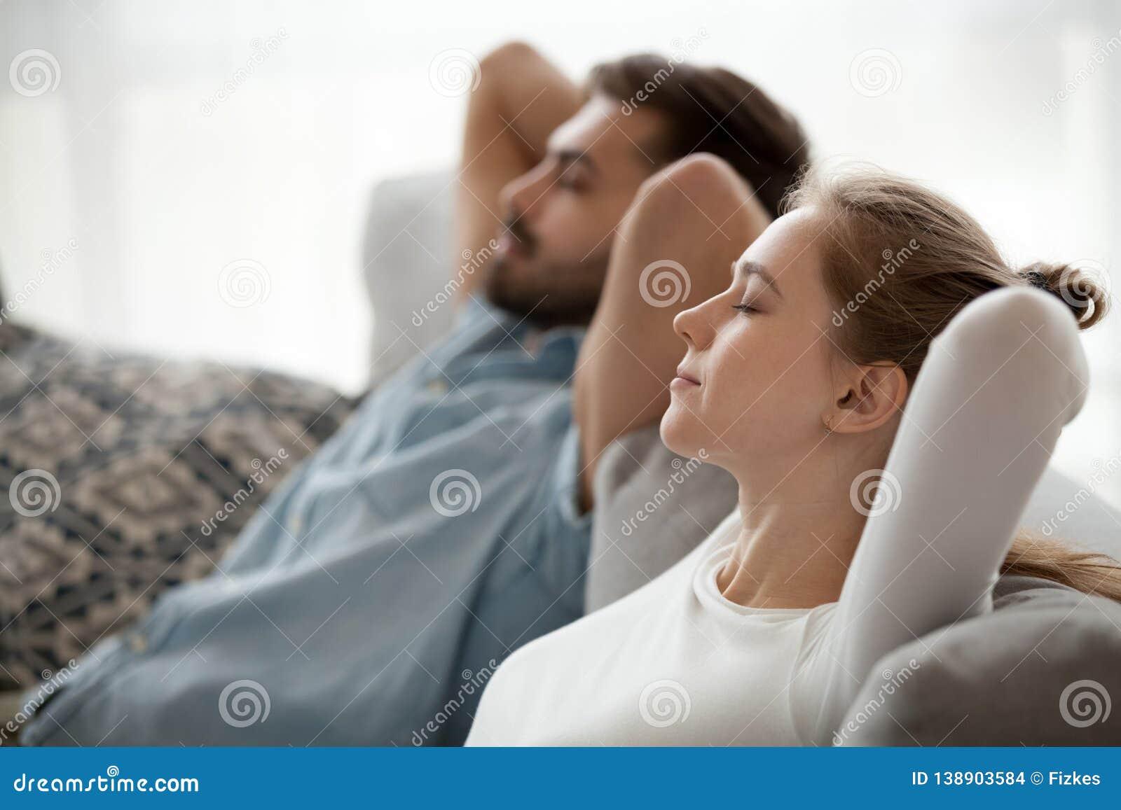 Pares calmos felizes que apreciam o abrandamento que tem a sesta no sofá que respira