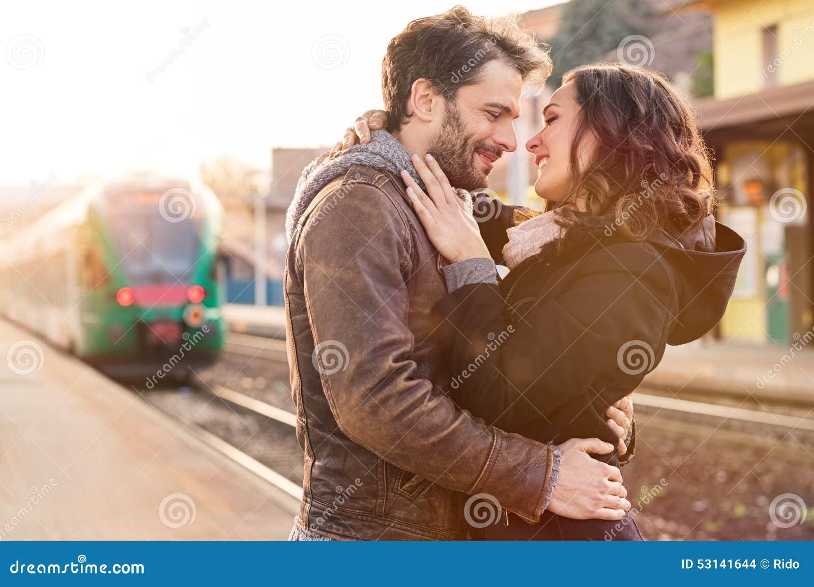 Pares cariñosos en la estación de tren