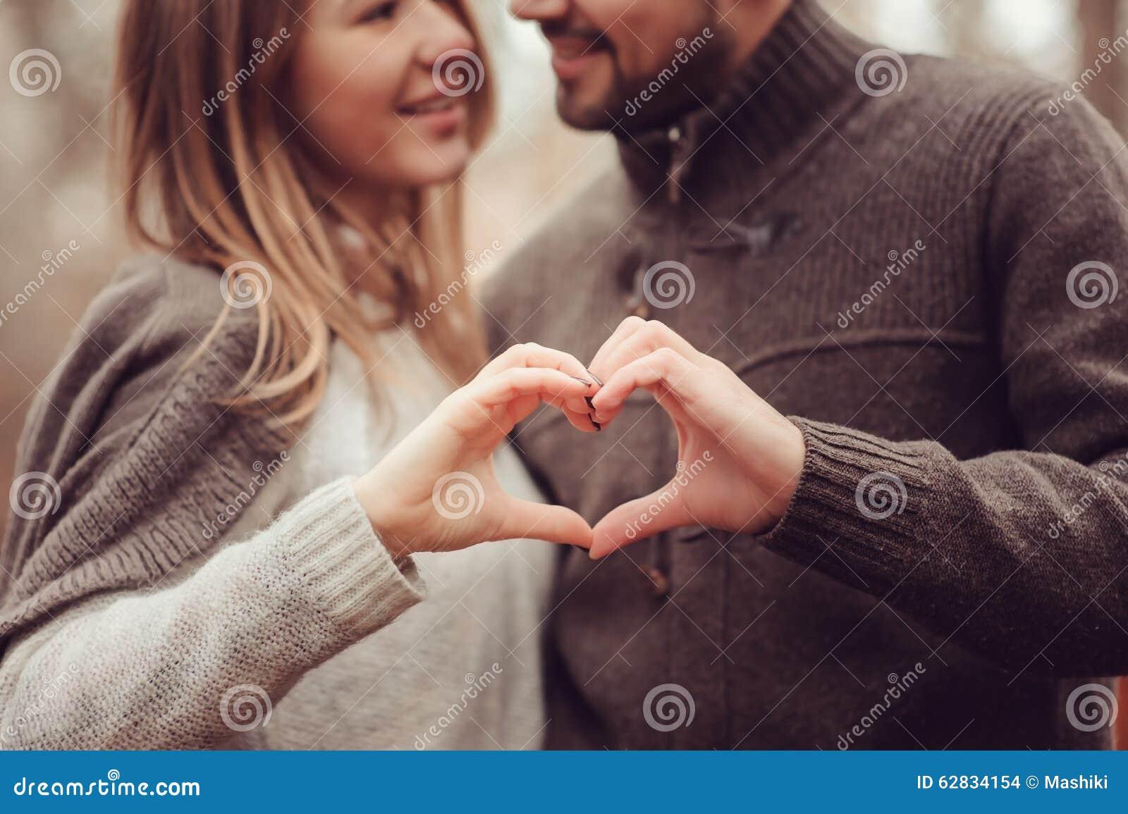 Pares cariñosos felices jovenes que muestran el corazón para el día de San Valentín en paseo al aire libre acogedor en bosque