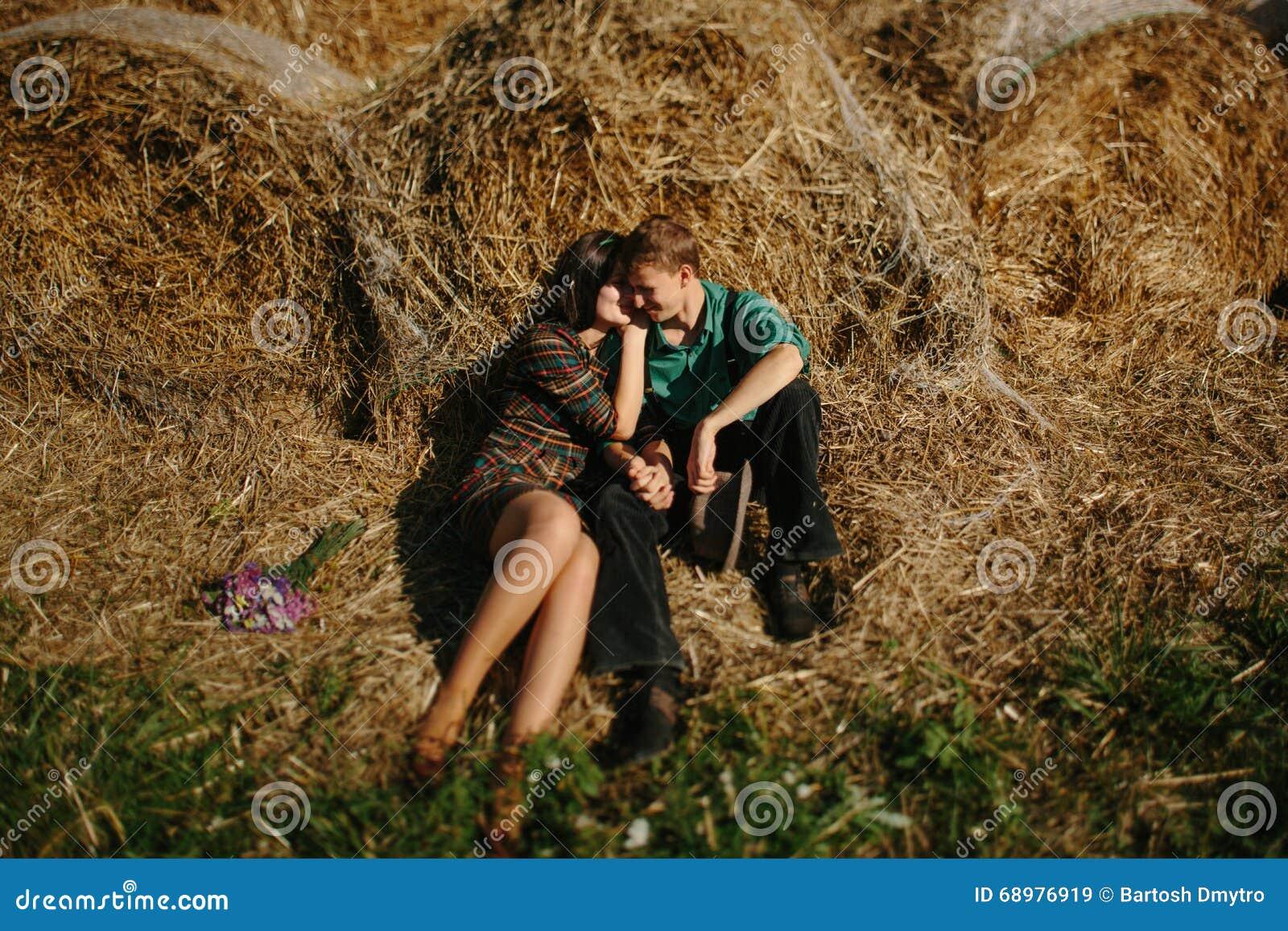 Pares cariñosos jovenes en campo de trigo