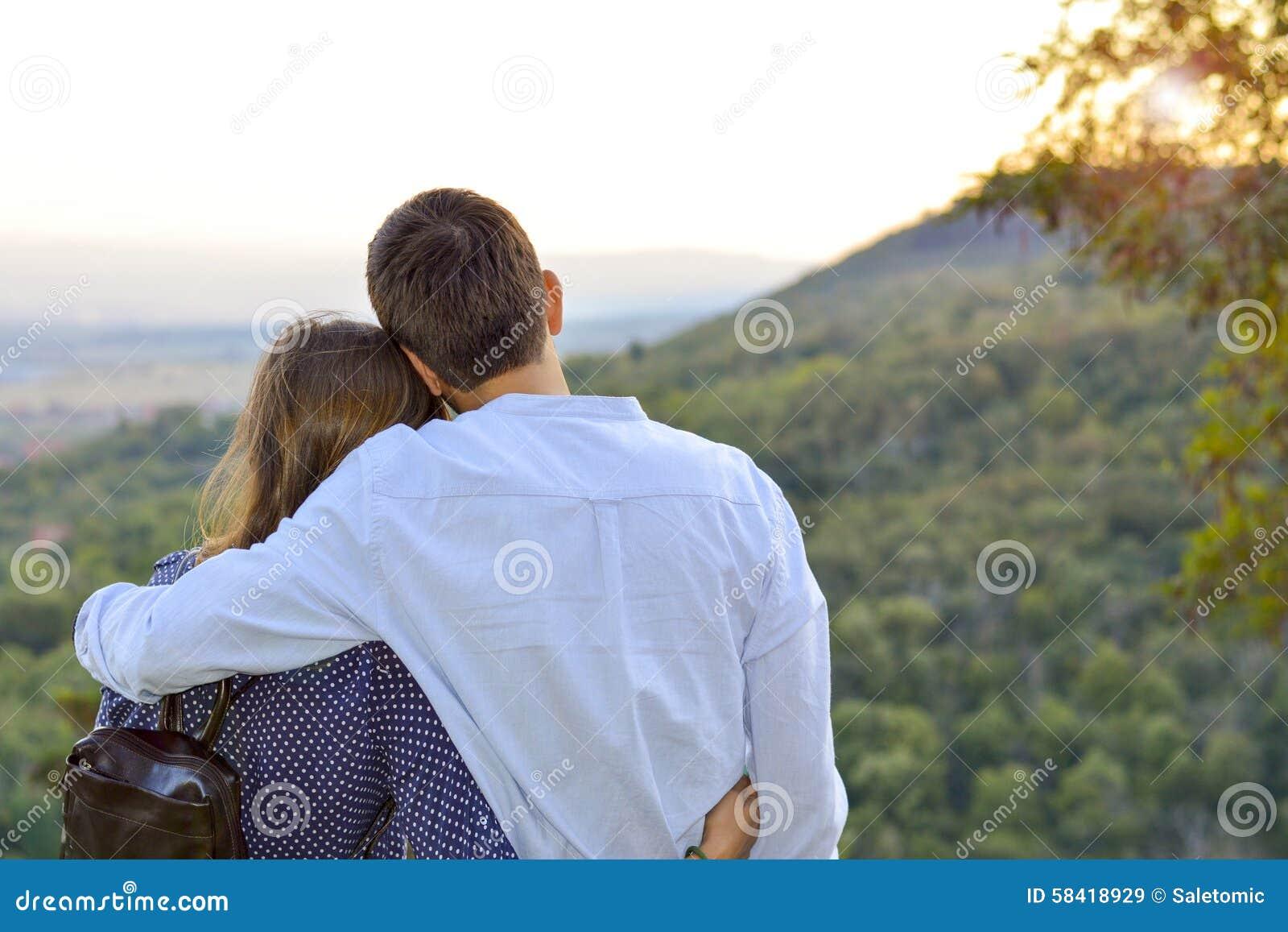 Pares cariñosos que abrazan al aire libre con la mirada en la puesta del sol roma