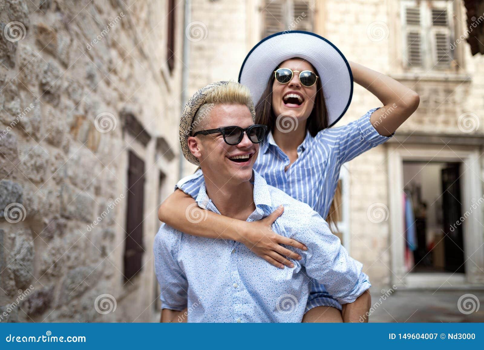 Pares cari?osos felices Hombre joven feliz que lleva a cuestas a su novia