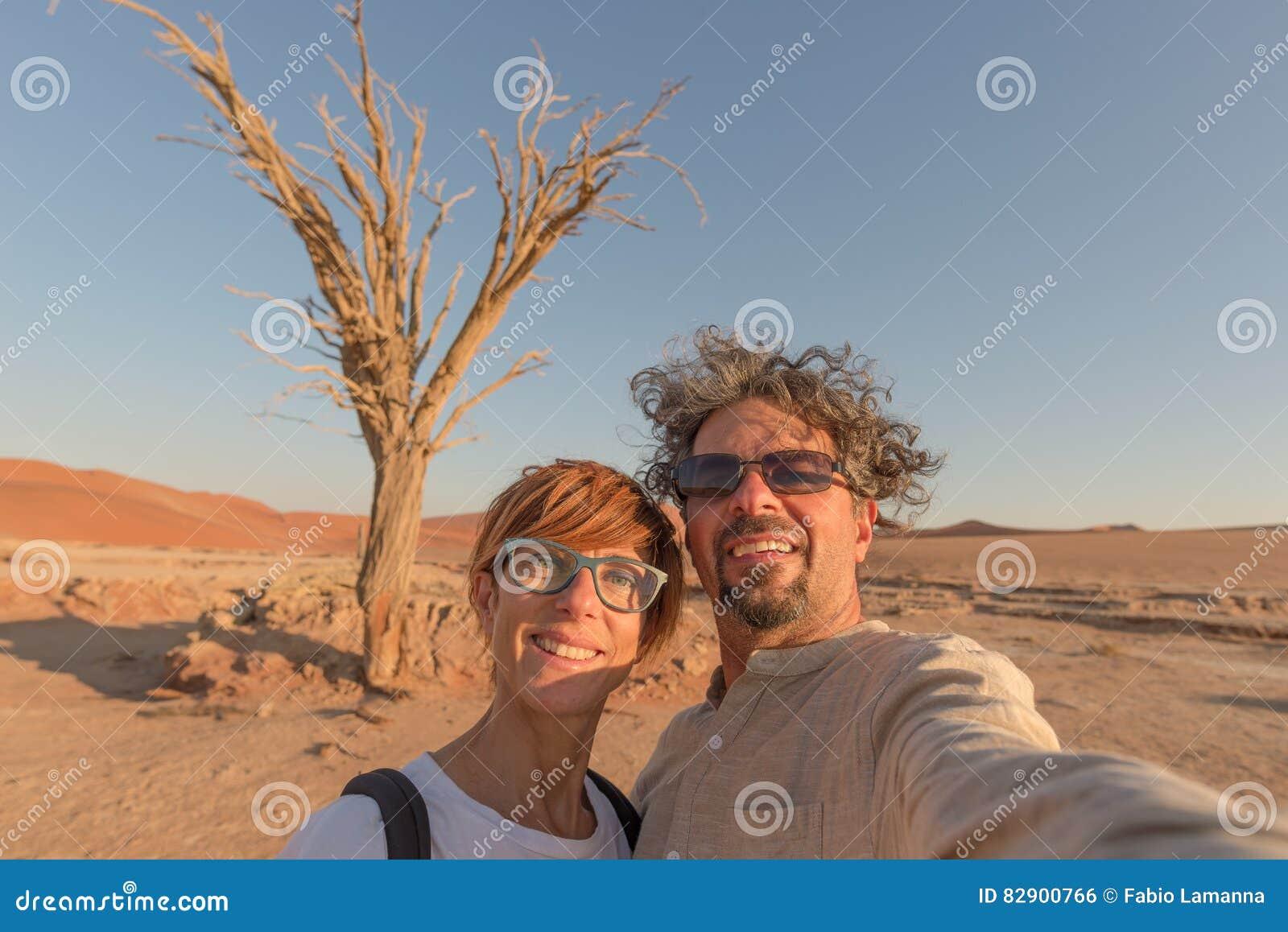 Pares caucasianos adultos que tomam o selfie em Sossusvlei no deserto de Namib, parque nacional de Namib Naukluft, destino princi