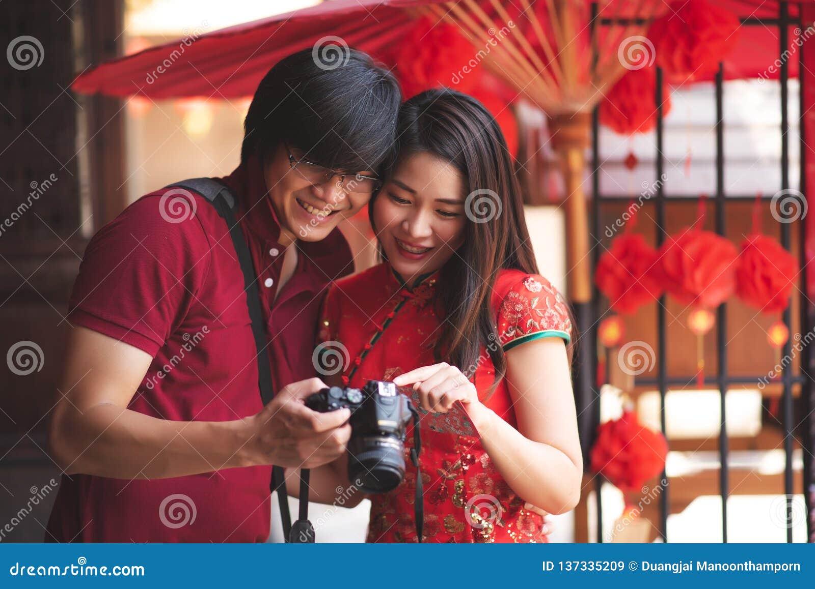 Pares chinos asiáticos felices que llevan el vestido y la camiseta rojos tradicionales de Cheongsam y que miran en cámara en viaj