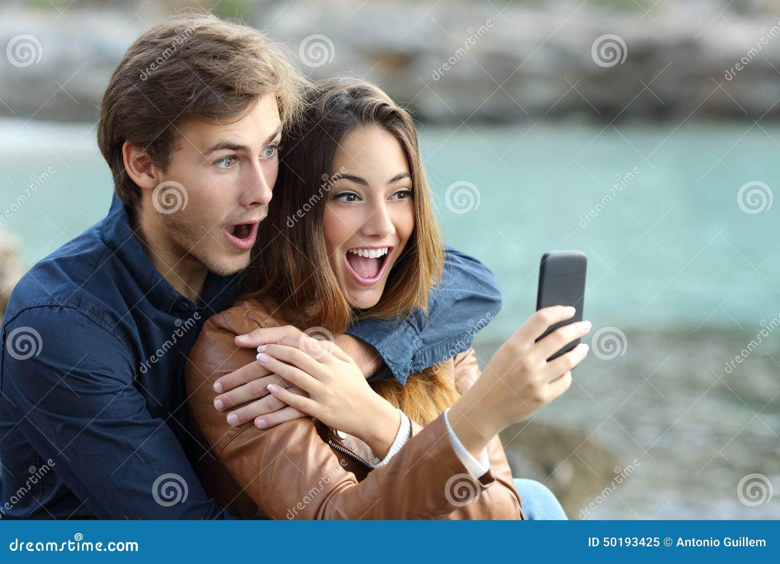 Pares chocados que miran un teléfono elegante el días de fiesta