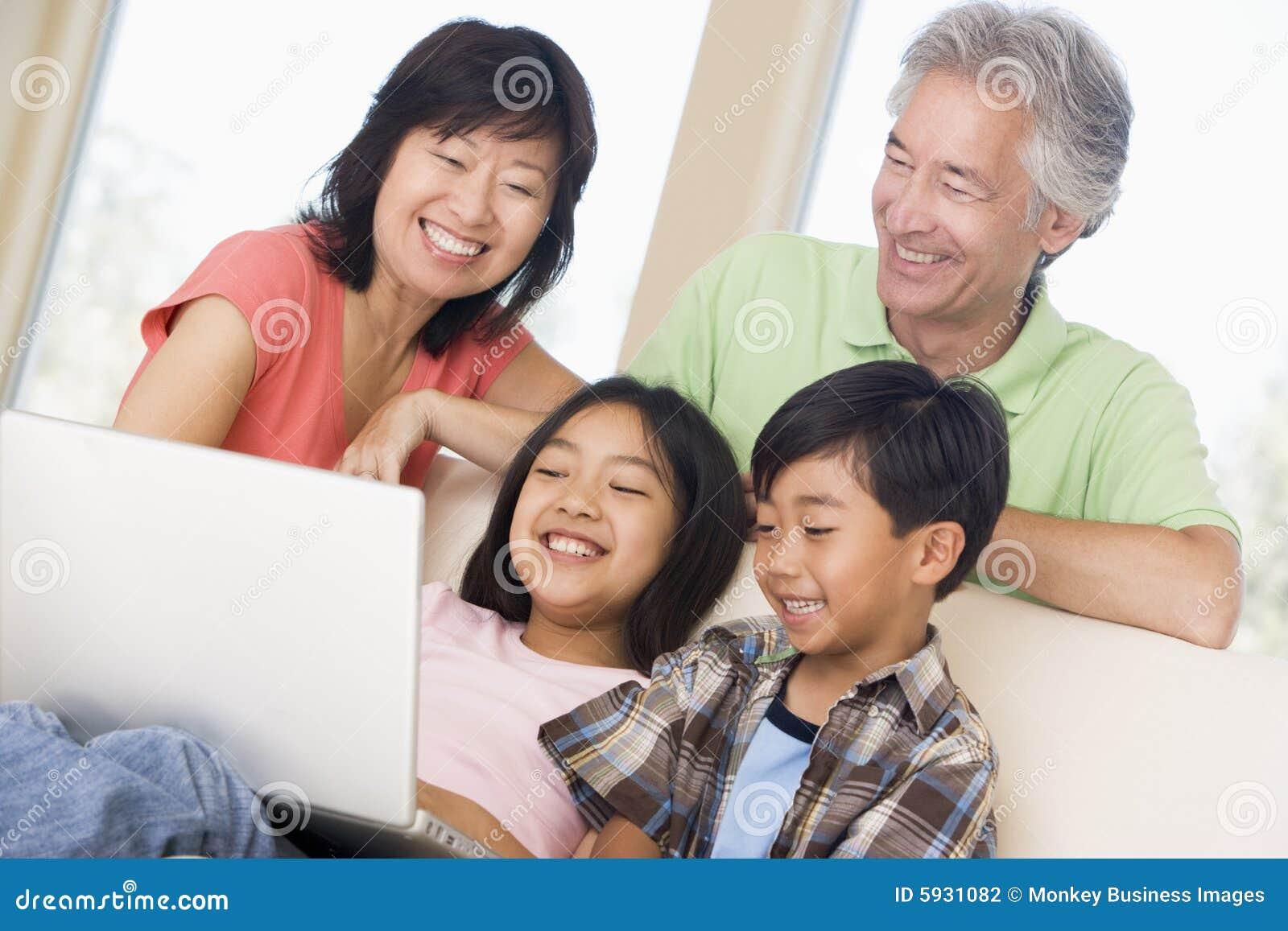 Pares com as duas crianças no quarto com portátil