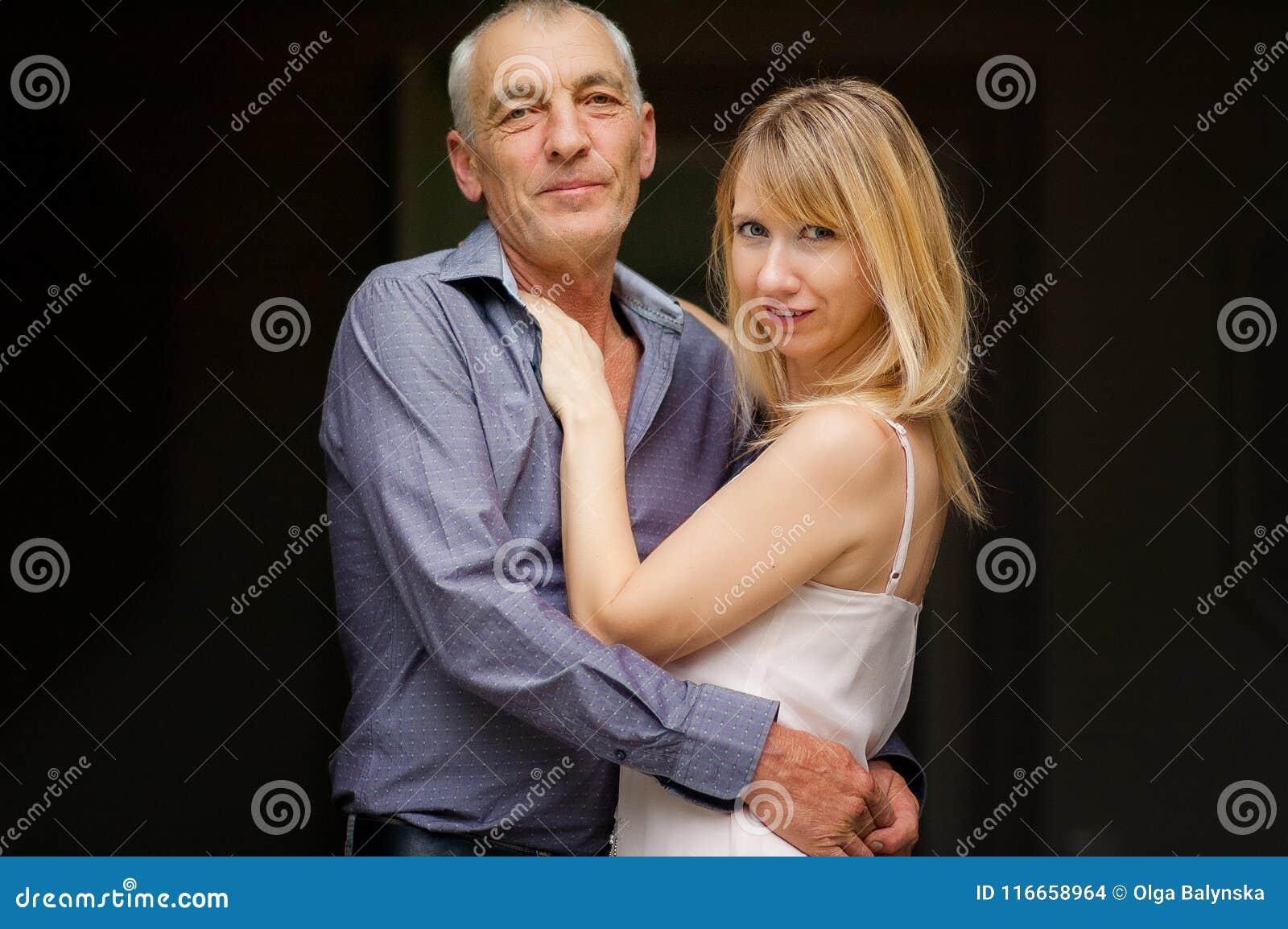 Pares com a diferença da idade que abraça no fundo preto Jovem mulher atrativa no vestido e no homem superior na camisa azul