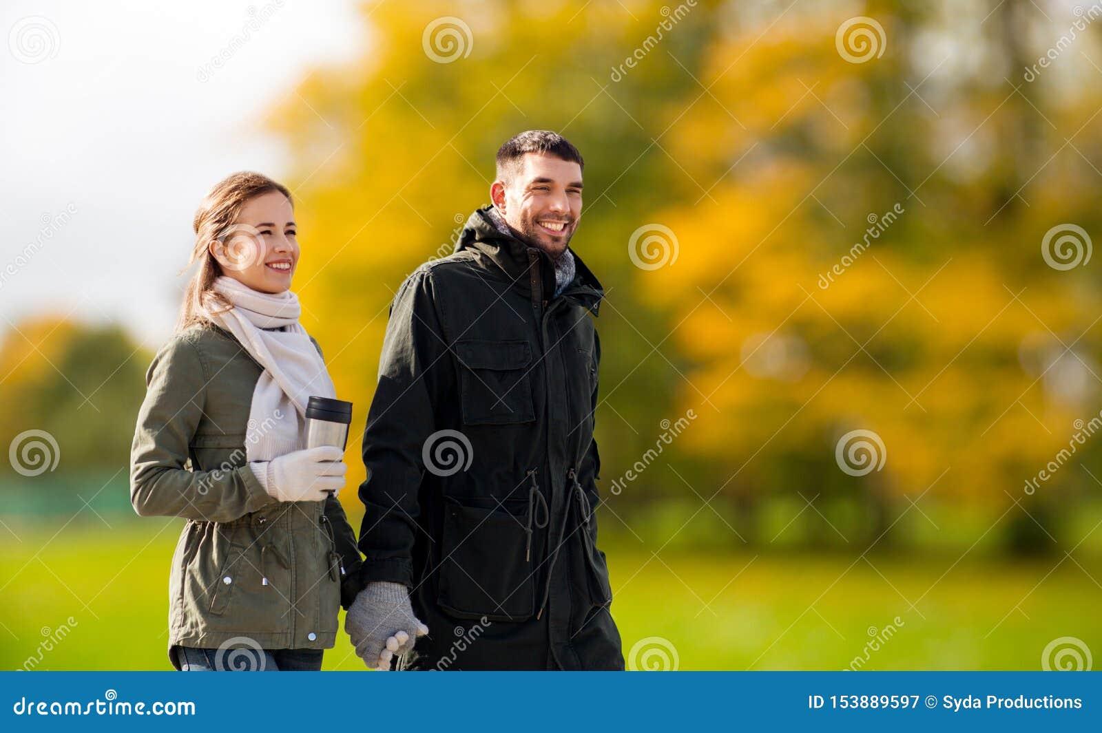 Pares com a secadora de roupa que anda ao longo do parque do outono