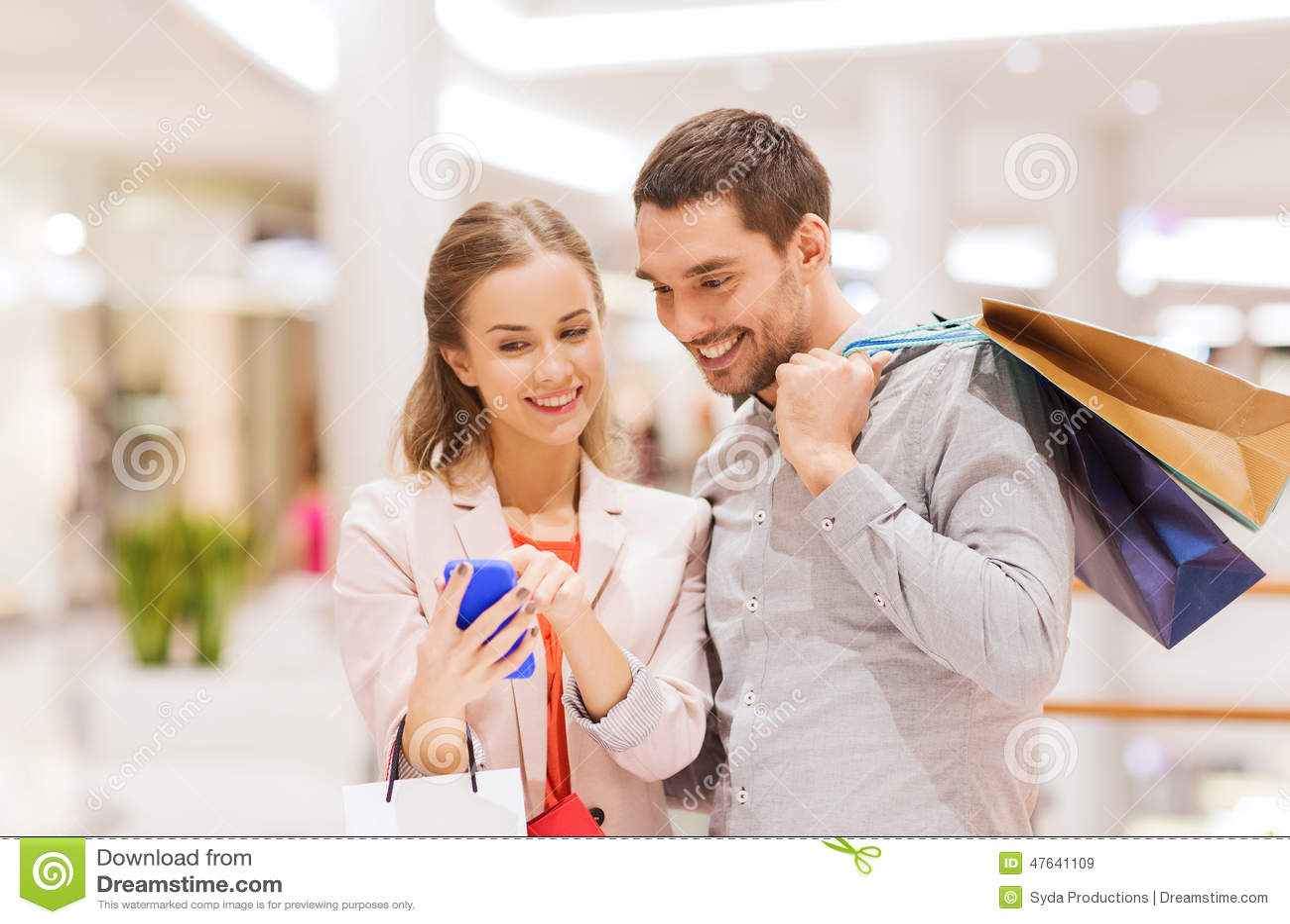 Pares com smartphone e sacos de compras na alameda