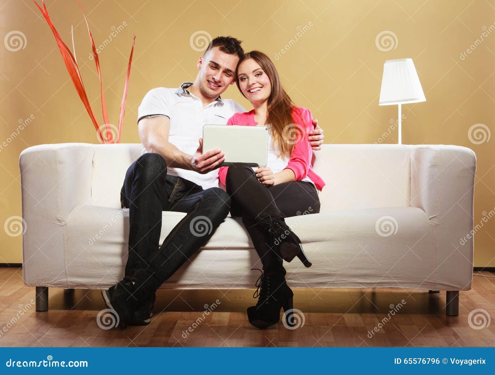 Pares com a tabuleta que senta-se no sofá em casa