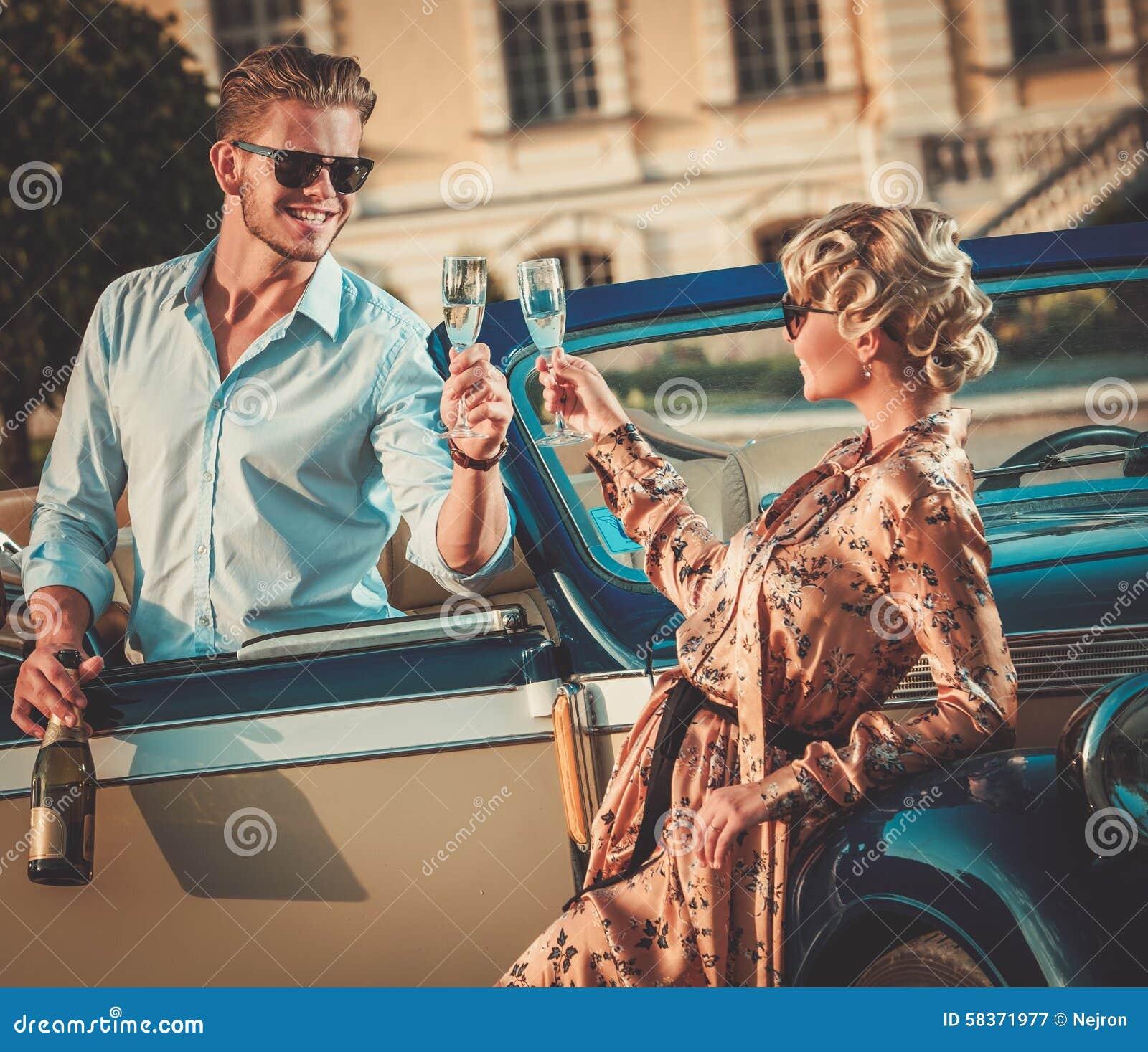 Pares con champán cerca del coche clásico