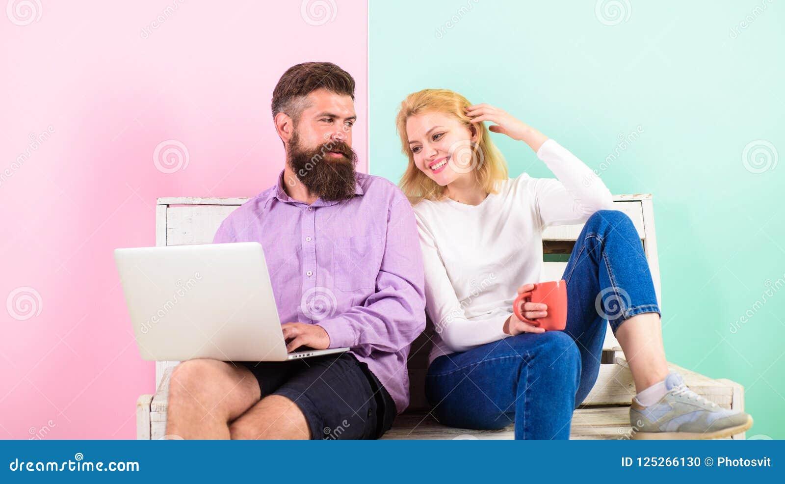 Pares con el ordenador portátil que va a mirar película La familia pasa el ocio junto Pares que eligen película de la comedia Par