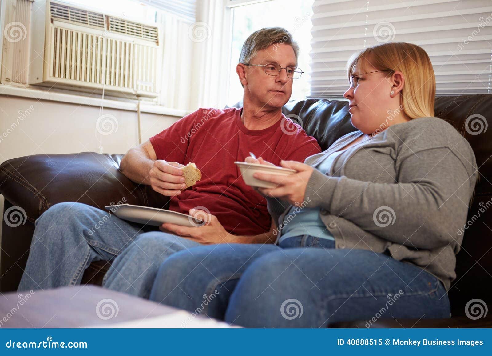 Pares con la dieta de los pobres que se sienta en Sofa Eating Meal