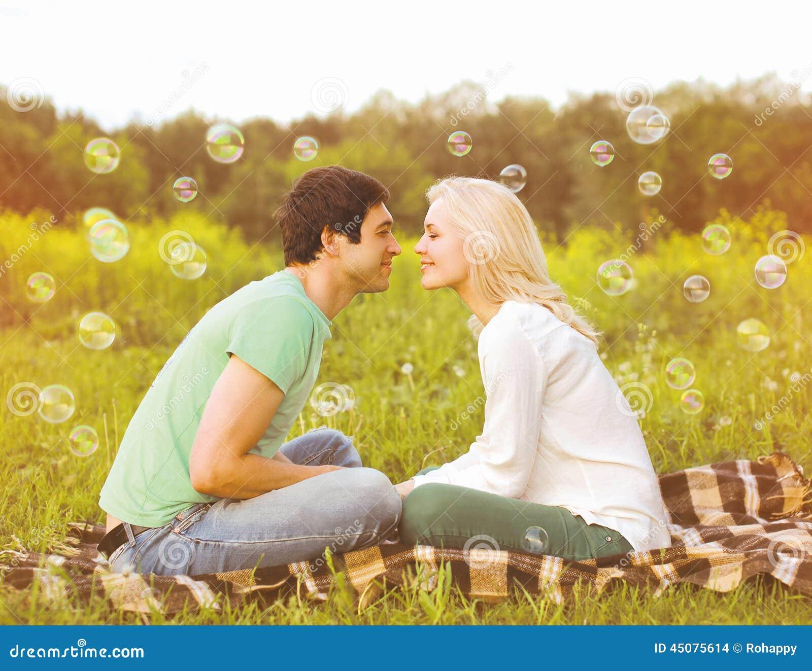 Pares consideravelmente românticos no amor que tem bolhas de sabão do divertimento