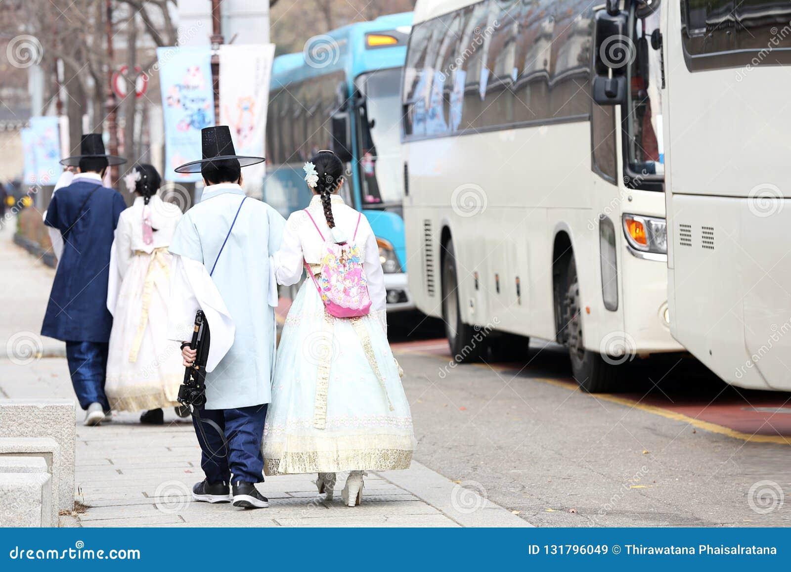 Pares coreanos que vestem um traje nacional Hanbok para tomar fotos no REI Kung Palace na queda do outono, o 16 de novembro de 20