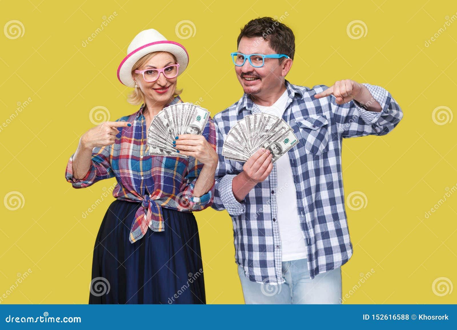 Pares de amigos ricos, del hombre adulto y de la mujer en la camisa a cuadros casual que se coloca junto que sostiene la fan de d
