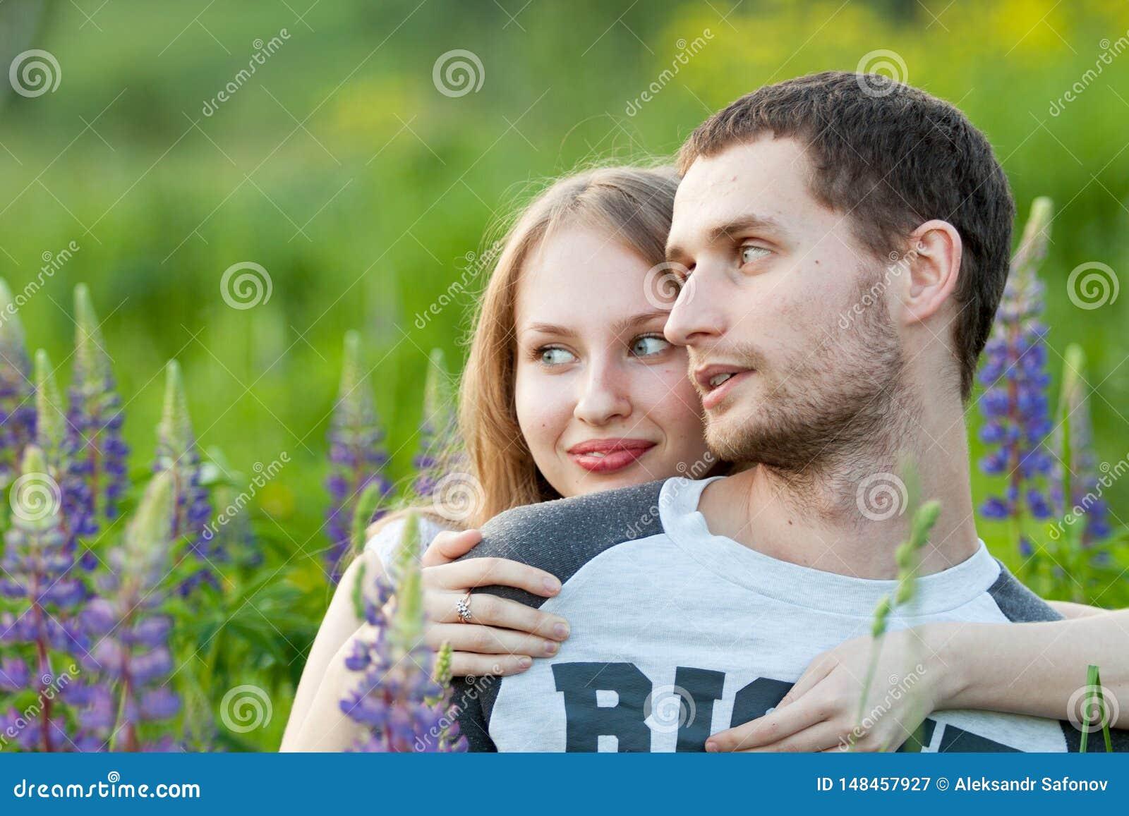 Pares de amor felizes que abraçam no campo do lupine