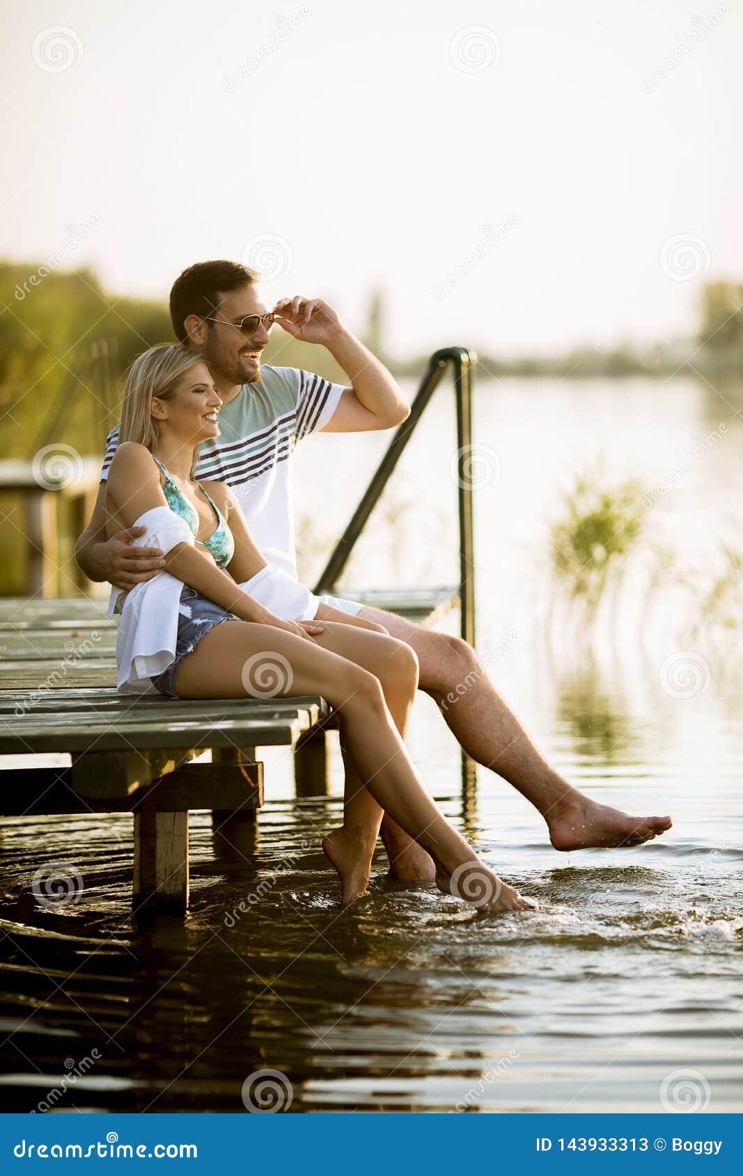 Pares de amor que sentam-se no cais no lago