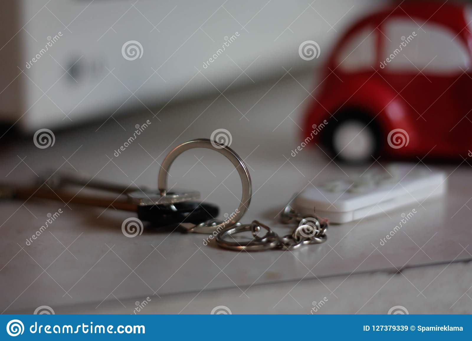 Pares de chaves com uma porta-chaves em uma tabela em um fundo de um carro vermelho